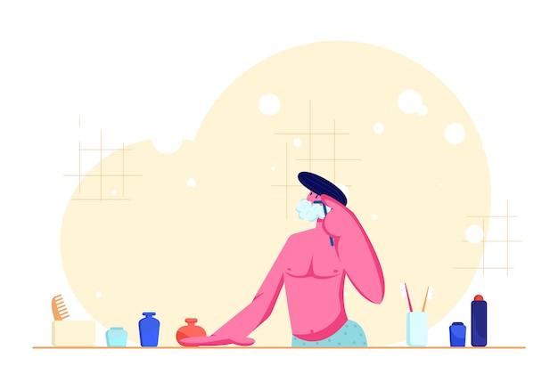 Młody mężczyzna z nagim tułowiem goli się w łazience, podając maszynkę do golenia brodę, patrząc w lustro