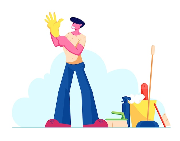 Młody mężczyzna założył żółtą gumową rękawicę na rękę stań w pobliżu narzędzi i sprzętu do czyszczenia
