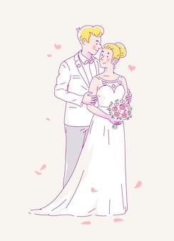 Młody pan młody w białym stroju i panna młoda w sukni ślubnej i kwiatach biorą ślub.