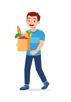 Młody przystojny mężczyzna niesie torbę pełną ilustracji spożywczych