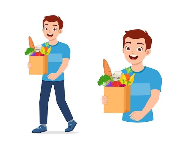 Młody przystojny mężczyzna niesie torbę pełną zakupów spożywczych