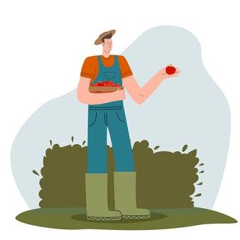 Młody rolnik ze świeżymi warzywami w boksieekologiczny projekt targu do sprzedaży produktów roln...