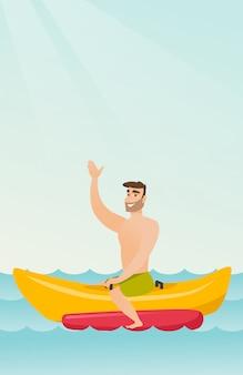 Młody szczęśliwy caucasian mężczyzna jedzie bananową łódź