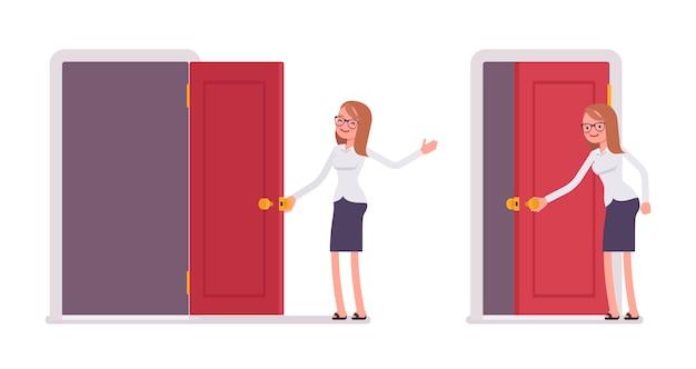 Młody uśmiechnięty żeński urzędnik otwiera czerwonego drzwi i wita