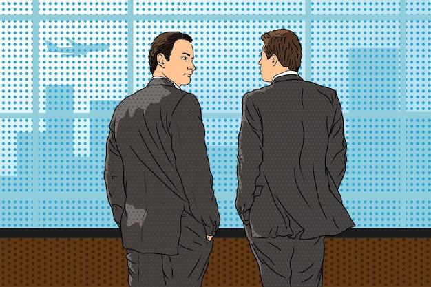 Młodzi biznesmeni w garniturach stoją w biurze przy oknie