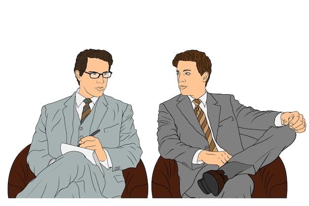 Młodzi biznesmeni w klasycznych garniturach siedzą na konferencji w fotelach