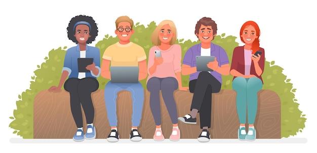 Młodzi ludzie siedzą na ławce z gadżetami. uczniowie do nauki używają laptopów, smartfonów i tabletów. uzależnienie od internetu. ilustracja wektorowa w stylu kreskówki