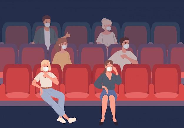 Młodzi ludzie siedzący w kinie w ochronnych maskach obserwują dystans społeczny