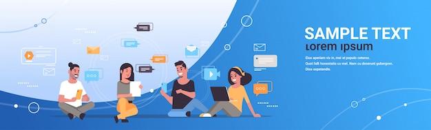 Młodzi ludzie używający cyfrowych gadżetów koncepcja sieci społecznościowej technologia komunikacji mężczyźni kobiety grupa rozmawiać online