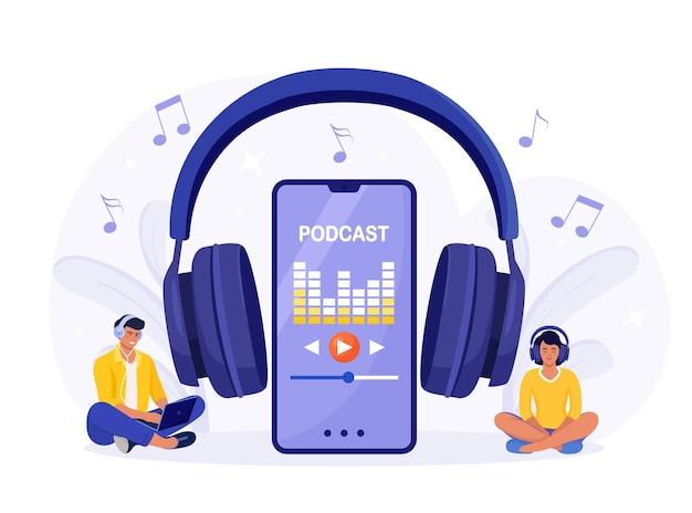 Młodzi ludzie w słuchawkach siedzą na podłodze i słuchają podcastu na smartfonie. internetowy program podcastów, radio. ludzie słuchający głośników ze stacji nadawczej. webinarium, szkolenie internetowe