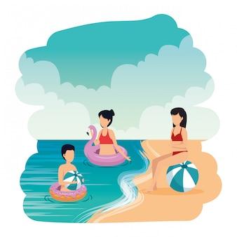 Młodzi ludzie z balonem i pływają na plaży