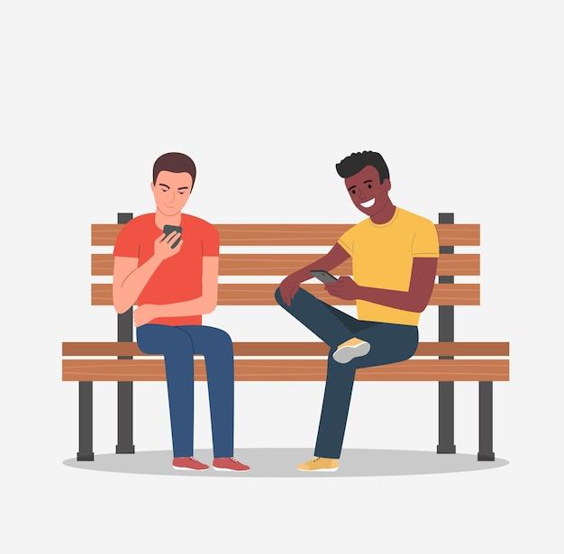 Młodzi mężczyźni siedzą na ławce ze smartfonami. ilustracja stylu płaskiej kreskówki