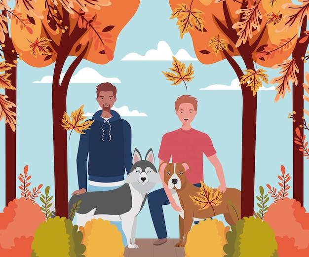 Młodzi mężczyźni z uroczymi maskotkami dla psów w obozie jesiennym