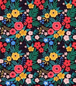 Modny kwiatowy wzór z jasnymi kolorowymi kwiatami i liśćmi na ciemnoniebieskim tle.