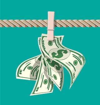 Mokre dolary wiszące na linie przymocowane szpilkami do ubrań. koncepcja prania pieniędzy. brudne pieniądze