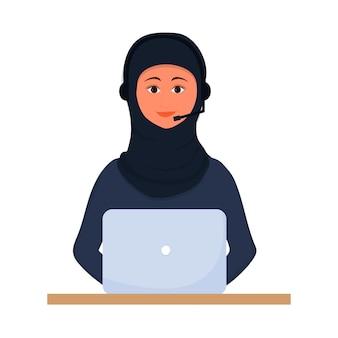 Muzułmańska arabka siedzi i pracuje z laptopem w tradycyjnych strojach hidżabu