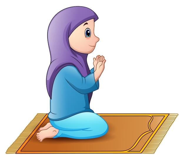 Muzułmańska dziewczyna siedzi na modlitewnym dywaniku podczas gdy ono modli się