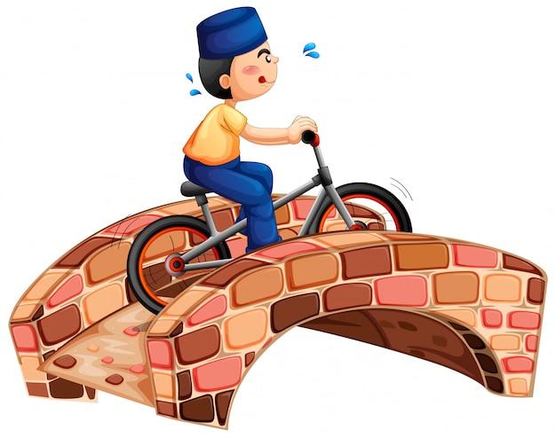Muzułmański chłopiec na rowerze przez most