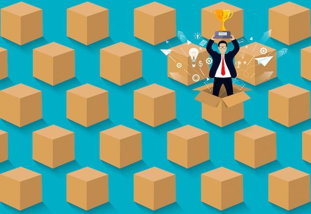 Myśl nieszablonowo. biznesmen stoi trzymając kubek z brązowym pudełku