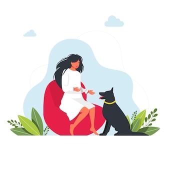 Na pufie siedzi dziewczynka, a obok niej duży pies. koncepcja pobytu w domu. brunetka dziewczyna siedzi i wyciąga rękę do psa. koncepcja zwierząt domowych. wektor. czas wolny z koncepcją zwierzaka
