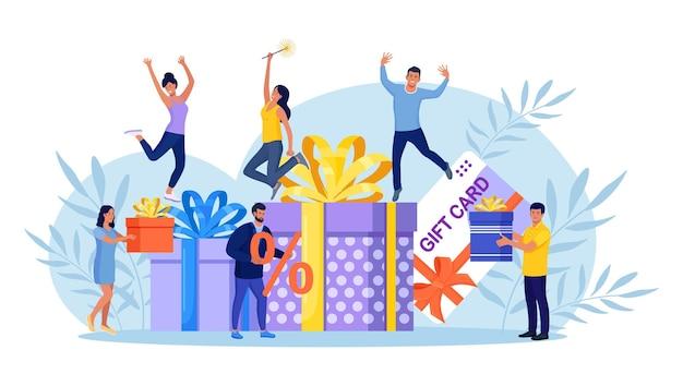 Nagroda online. ludzie otrzymują pudełko upominkowe. internetowi klienci detaliczni z kartą podarunkową, bon upominkowy, kupon rabatowy i bon upominkowy, cyfrowy program polecający. promocja sklepu internetowego, bonus