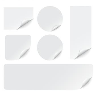 Naklejki papierowe z zawiniętymi rogami na białym tle