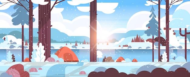 Namioty pole namiotowe w lesie zimowy obóz koncepcja słoneczny dzień wschód słońca śnieżny krajobraz przyroda z wodnymi górami i wzgórzami