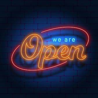 """Napis """"jesteśmy otwarci"""" na ścianie z cegły"""