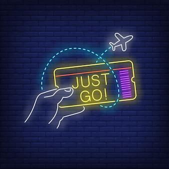 Napis just go neon i ręka trzymająca bilet lotniczy