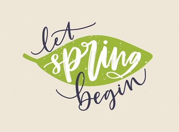Napis let spring begin napisany kaligraficzną kursywą i ozdobiony świeżym zielonym liściem.