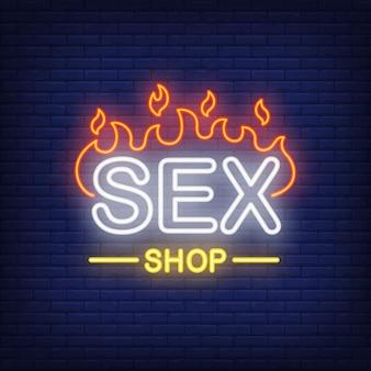 Napis na sex shopie w ogniu. neonowy znak na ceglanym tle.