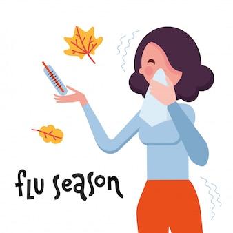 Napis na sezon grypowy i kobieta z katarem, dmuchająca nos chusteczką.