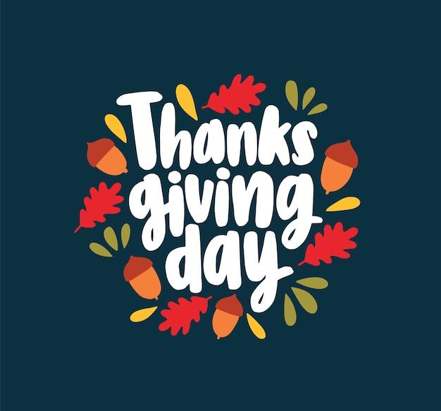 Napis na święto dziękczynienia napisany elegancką kursywą kaligraficzną czcionką i ozdobiony opadłymi jesiennymi liśćmi i żołędziami