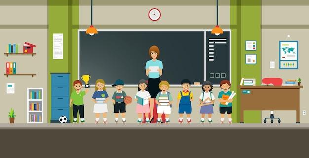 Nauczyciele i uczniowie stoją przed klasą z tablicą.