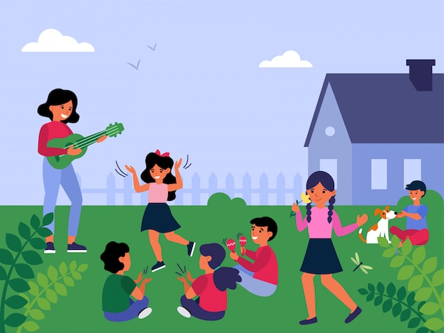 Nauczycielka gra na gitarze dla dzieci grających na zewnątrz