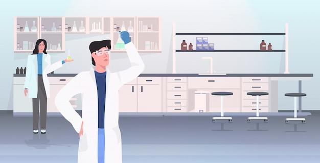 Naukowcy dobierają się trzymać próbne tubki pracuje w medycznym lab