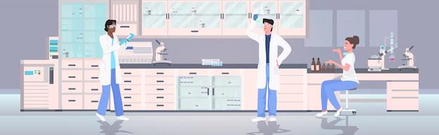 Naukowcy posiadający probówki pracujące w laboratorium medycznym