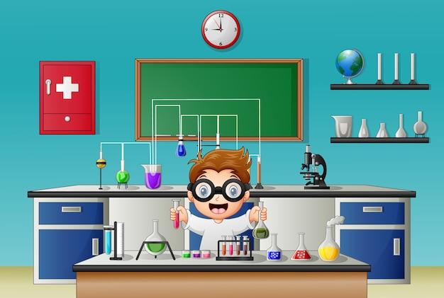 Naukowiec chłopiec w laboratorium badania z chemicznych wyrobów ze szkła