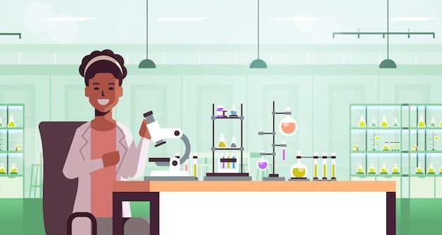 Naukowiec za pomocą mikroskopu i probówek