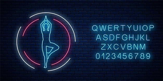 Neon świecące znak klubu ćwiczenia jogi w ramce koło z alfabetem na tle ciemnego ceglanego muru. oświetlenie uliczne szyld chińskiej gimnastyki. ilustracja wektorowa.
