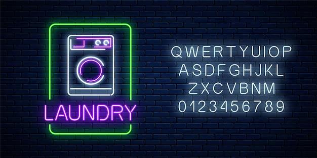Neon świecący szyld do prania z alfabetem na tle ciemnej cegły ściany. podświetlany znak myjni samoobsługowej działający całą dobę