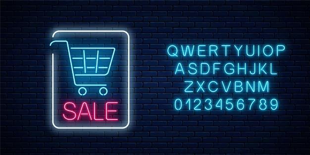 Neon świecący znak sprzedaży z koszykiem i alfabetem na ciemnym tle ceglanego muru. transparent neonowy rabat na duży sezon.