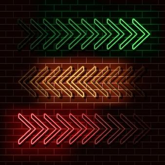 Neonowe zielone, żółte i czerwone strzałki na ścianie z cegły.