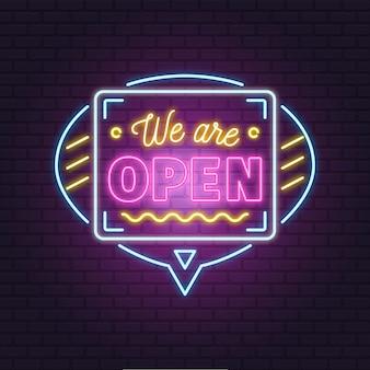 """Neonowy napis """"we are open"""" na ceglanej ścianie"""