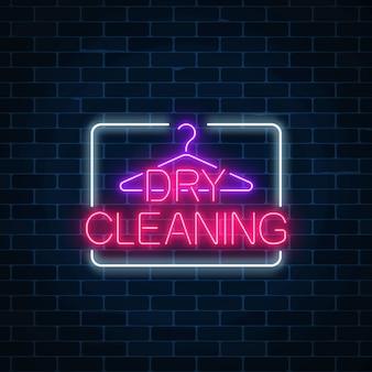 Neonowy pralni chemicznej rozjarzony znak z wieszakiem na ciemnym ściana z cegieł