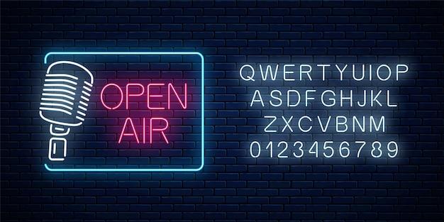 Neonowy szyld na świeżym powietrzu z mikrofonem i alfabetem