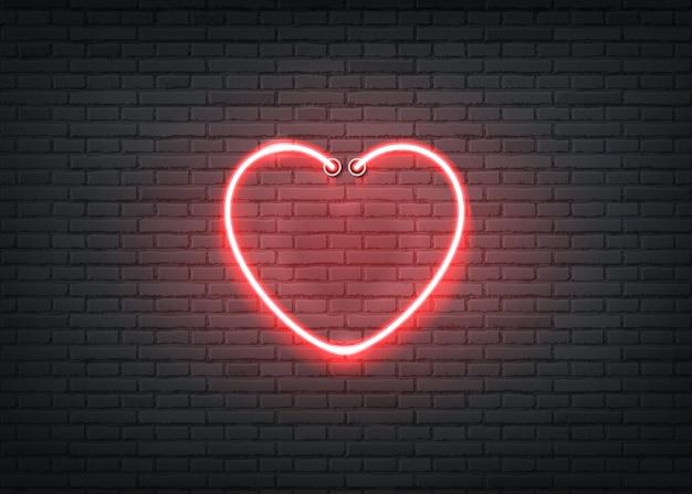Neonowy znak serca na tle ciemnej cegły ściany