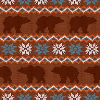 Niedźwiedź brunatny i płatki śniegu. zimowy wzór z dzianiny wełniane
