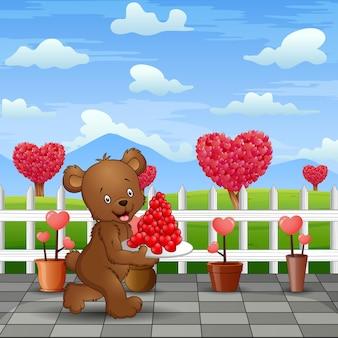 Niedźwiedź niosący talerz czerwonego serca w parku drogowym