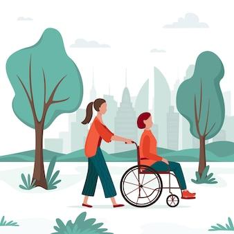 Niepełnosprawna kobieta na wózku inwalidzkim spacerująca po parku miejskim z osobą towarzyszącą. aktywność na świeżym powietrzu. pracownik socjalny lub wolontariusz z seniorami.